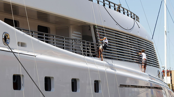 man suspended from rope cleaning the side of large yacht